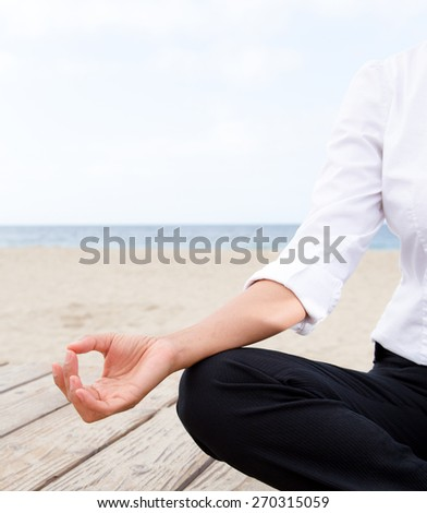 Asian woman in working outfit practicing yoga at beach
