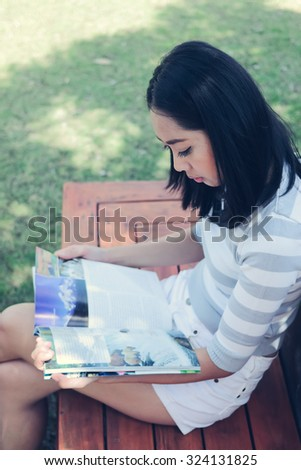 Asian woman is reading a magazine in the garden. - stock photo