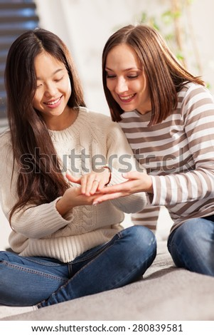 Asian woman is showing her ring to a friend - stock photo