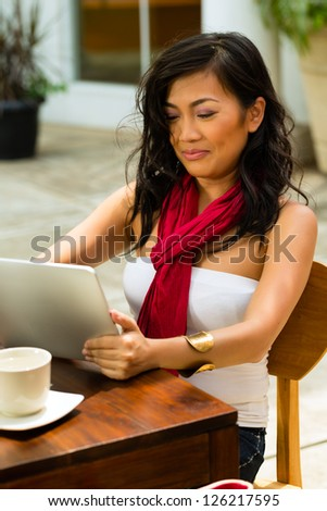 Asian woman is sitting in a bar or cafe outdoor and is surfing the internet with a tablet computer - stock photo