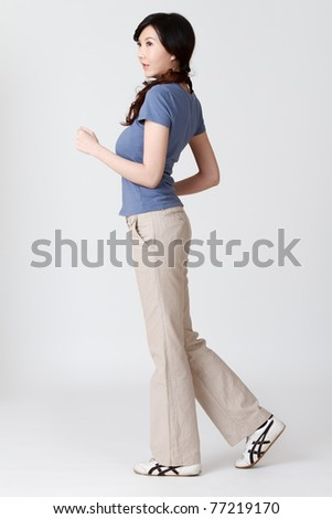 Asian woman jogging, full length portrait isolated on gray studio background. - stock photo