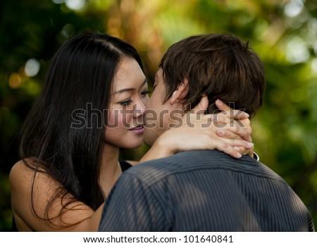 asian woman kissing caucasian man - stock photo