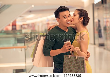 Asian woman kissing her boyfriend in the store - stock photo