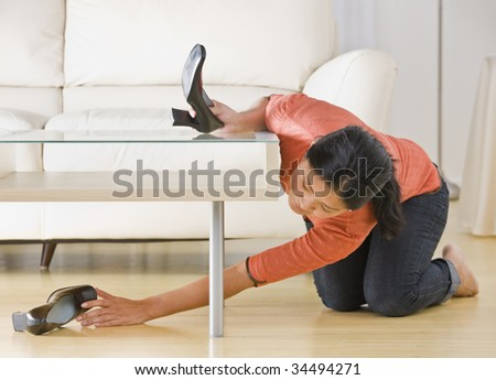 Asian woman kneeling on floor and reaching for shoe under coffee table. Horizontal. - stock photo