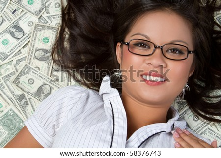 Asian woman laying in money - stock photo