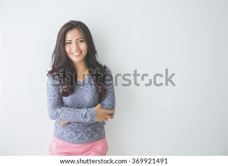 Asian woman leaning on a white wall. Casual woman crossed arm smiling looking happy in grey sweater