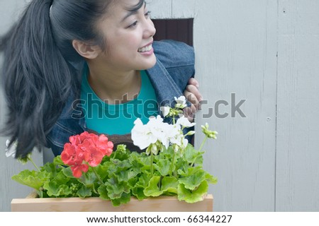 Asian woman leaning out window with flowerbox - stock photo