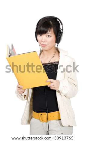 Asian woman learning in headphones with yellow book - stock photo