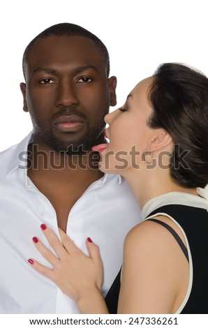 Asian woman licks his cheek dark-skinned men isolated on white - stock photo