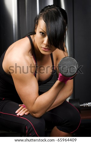 Asian woman lifting weights in gym - stock photo