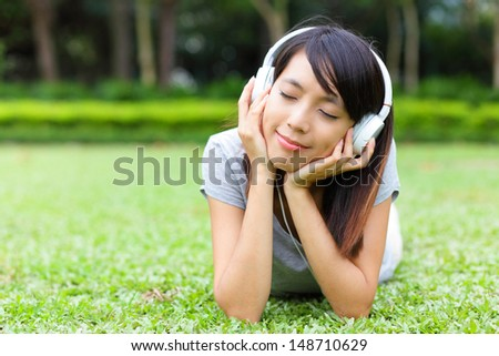 Asian woman listen to song lying on grass - stock photo