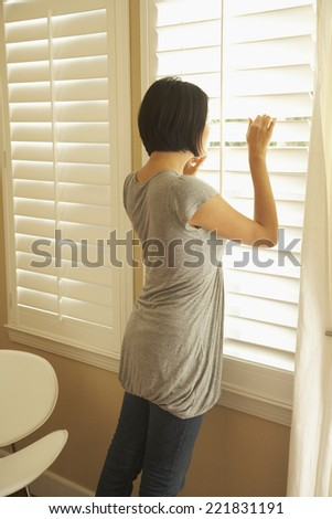 Asian woman looking out window - stock photo