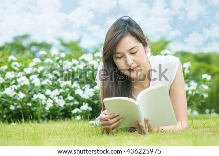Asian woman lying on grass field for reading a white book in the park