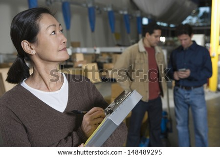 Asian woman making notes with workers in background at distribution warehouse - stock photo