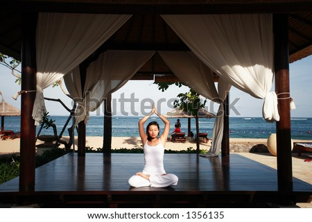 Asian woman meditating at the hotel's gazebo - stock photo