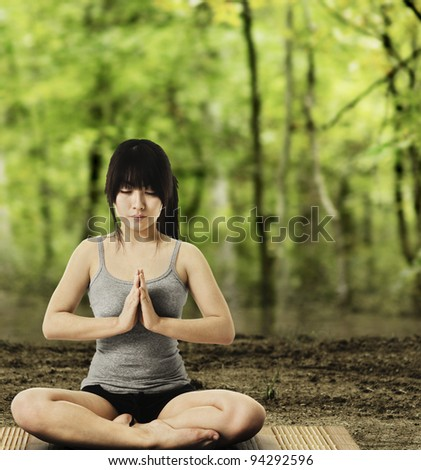 Asian woman on a yoga mat doing the salutation seal pose in a forest. Meditation.