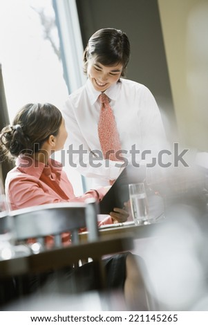 Asian woman ordering in restaurant - stock photo