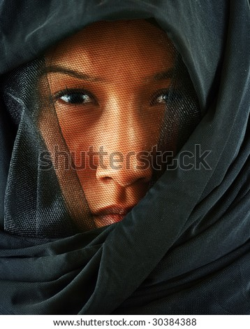 Asian woman peeking out from behind veil