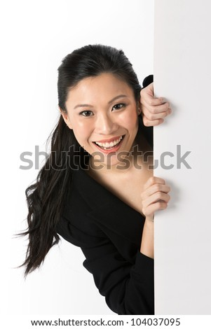 Asian woman peering around from behind a white wall. - stock photo