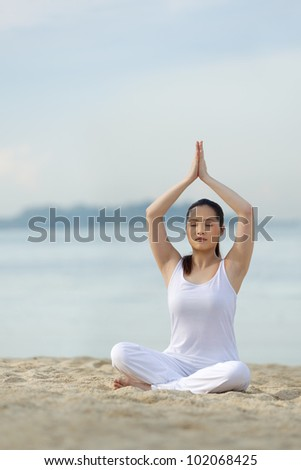 Asian woman performing yoga on a tropical beach