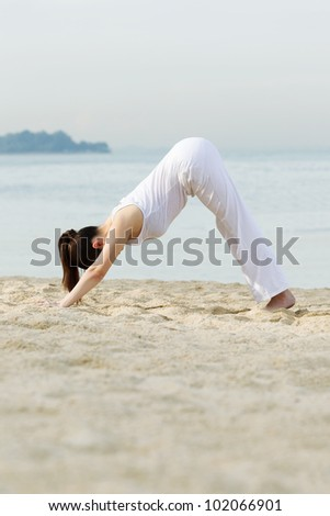 Asian woman performing yoga on beach with sea in background.