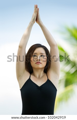 Asian woman performing yoga with sky and palm trees in background.