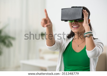 Asian woman playing game in virtual reality glasses - stock photo