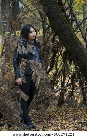 Asian woman poses in the park, in a forest in autumn Fashion a black jacket