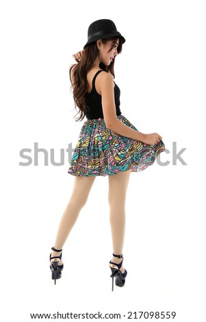Asian woman posing in a black vest top and graphic print waver pleated skirt with black hat isolated on white background.