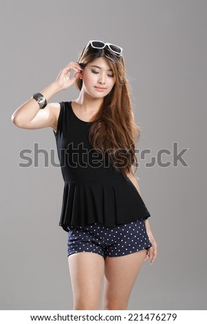 Asian Woman posing in Black Round Neck Sleeveless Peplum Top and Polka-dot Shorts.