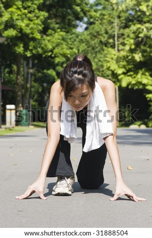 asian woman preparing to start a short sprint in a park - stock photo