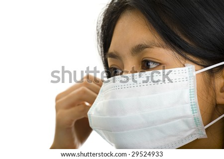 asian woman putting on a face mask - stock photo