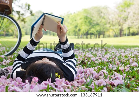 Asian woman reading booklet on the grass - stock photo