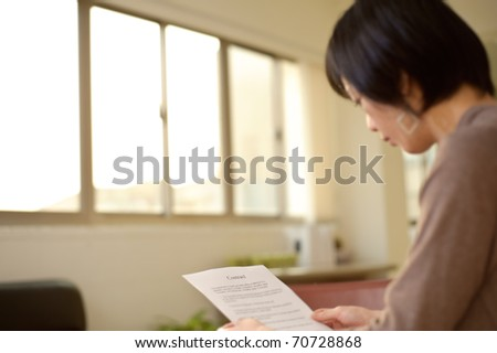 Asian woman reading business contract on desk in office, focus on paper.