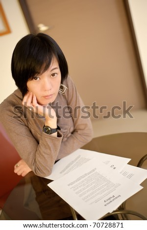 Asian woman reading insurance policy paper on desk in office.
