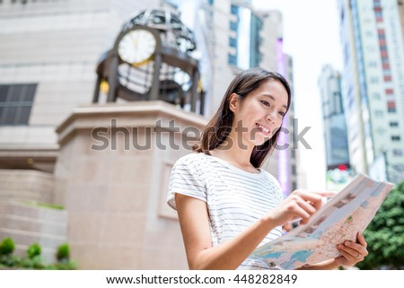 Asian woman reading on city map - stock photo