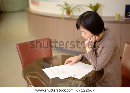 Asian woman reading paper on desk in office.