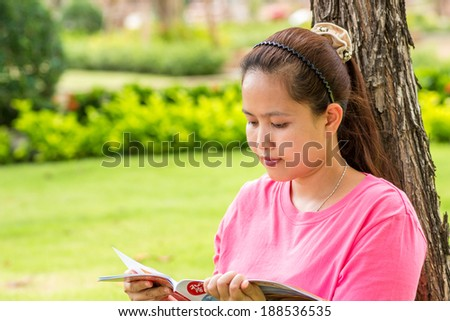 Asian woman reading travel magazine book in park. - stock photo