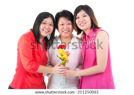 Asian woman receiving carnation flower from daughters on mothers day - stock photo