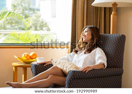 Asian woman relaxing in armchair - stock photo