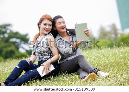 asian woman relaxing in the park look tablet