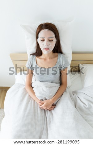 Asian woman resting on bed and using paper mask