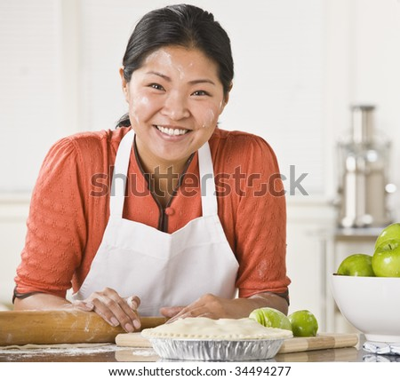 Asian woman rolling dough, making pie, smiling at camera with flour on her face. Square. - stock photo