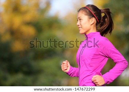 Asian woman running in autumn forest in fall. Female runner training outdoor in warm running outfit. Beautiful multi-ethnic Chinese Asian / Caucasian female jogging. - stock photo