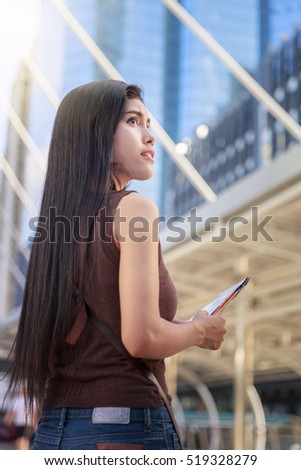 Asian Woman Sightseeing In City And Holding A Map