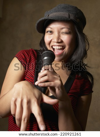 close up of asian woman singing into microphone stock