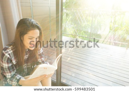 asian woman sit and reading book near the window with afternoon sun light