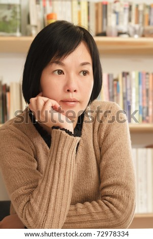 Asian woman sitting and thinking at home.