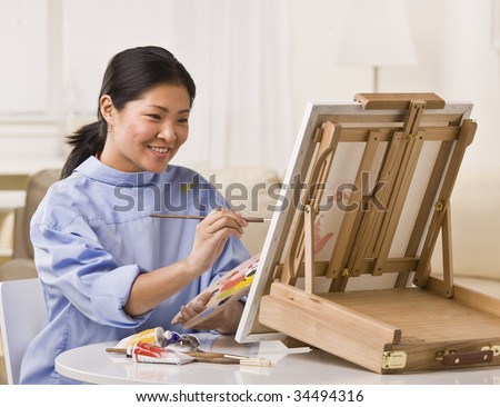 Asian woman sitting at table, smiling and painting on small easel. Horizontal - stock photo