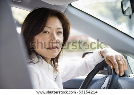 Asian woman sitting in car at steering wheel. - stock photo
